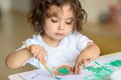Portrait Cute Little Girl Drawing With Green Paint On Fall Lives. Curly Adorable Child Painting At T poster