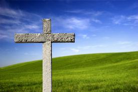 stock photo of christian cross  - Religious stone cross on a beautiful green hill - JPG