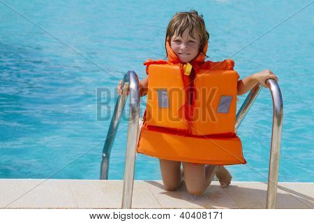 young happy smiling child girl in inflatable life-jacket swimming in pool