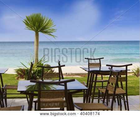 table and chairs in outdoor restaurant on tropical beach