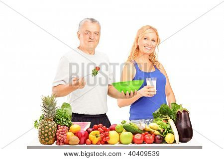 Two mature persons consuming healthy products behind a table full of fruits and vegetables isolated on white background