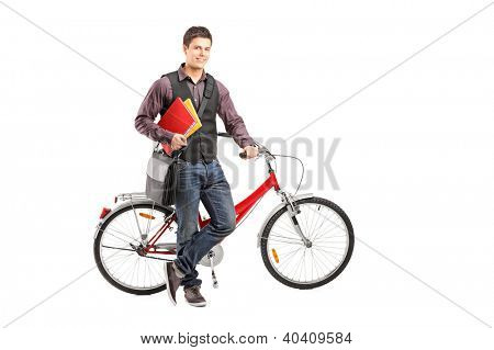 Full length portrait of a smiling student holding books next to a bike isolated on white background