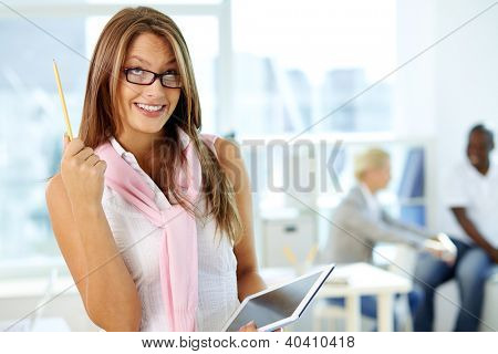 Portrait of cute secretary with touchpad looking and pointing upwards
