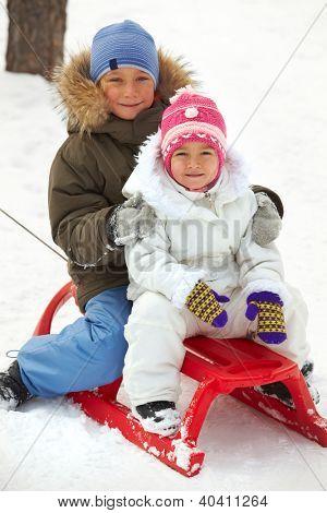 Happy siblings in winterwear tobogganing in park