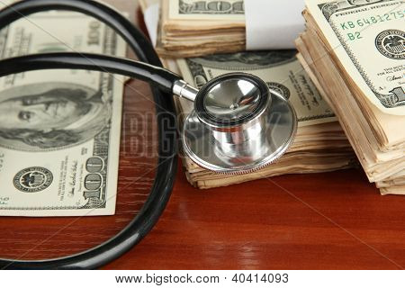 Healthcare cost concept: stethoscope and dollars on wooden background