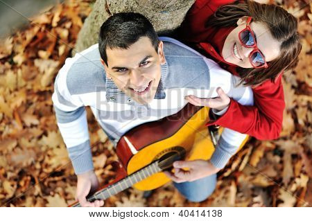 Romantic couple with guitar in park