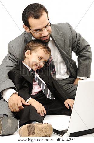 Portrait of a happy young man and his son working on laptop