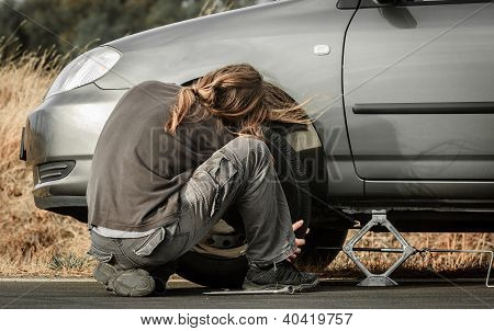 Young man repairing car outdoors on the road