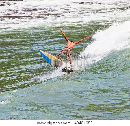 BALI, INDONESIA - JANUARY 13: Unidentified young surfer on the board on January 13, 2012. Dreamland beach, Bali, Indonesia. The Dreamland is one of the most popular surfing areas of Bali.
