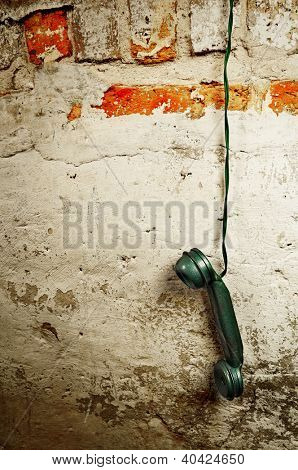 Retro Phone Cord - Vintage Telephone Handset Receiver hanging by the Cord down a Brick Wall