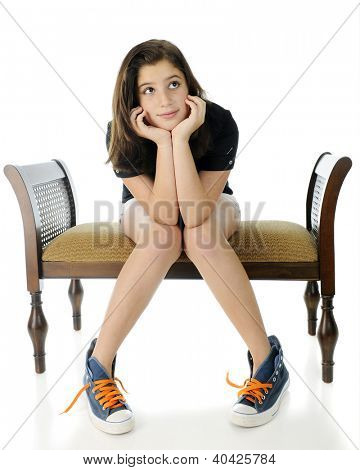 A pretty preteen wistfully sitting on a bench, her head propped by her hands, knees together and feet spread.  She's wearing shorts and over-sized, unlaced high-top sneakers.  On a white background.
