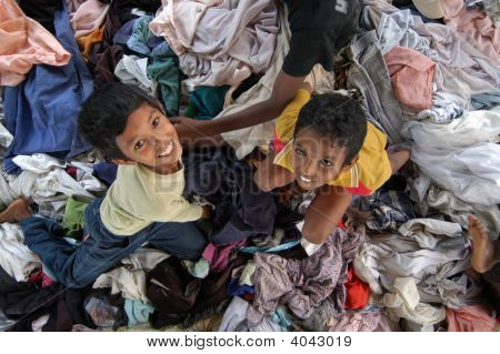 Kids In Clothing Pile