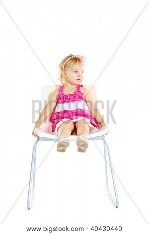 Pretty little girl sitting on a chair. Isolated over white background.