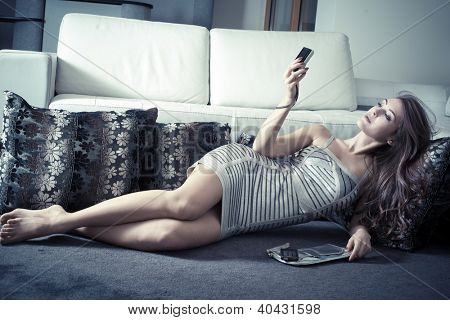 elegant young voman in living room lie on carpet take picture of herself  with digital camera