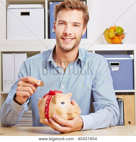 Smiling young man saving his Euro money in a piggy bank
