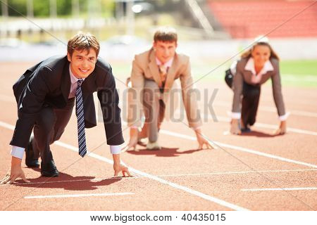 Businessmen running on track racing at athletich stadium