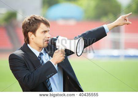 Businessman in black suit with loudspeaker at athletic stadium