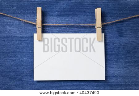 White Blank Paper Card Hanging Over Wood Background