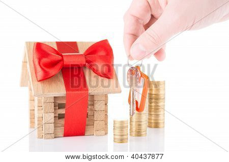 wooden house, coins and keys in a hand