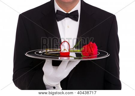 A butler holding a silver tray upon which is a diamond engagement ring in a heart shaped jewelry box and a single red rose, on a white background.