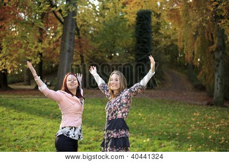 Happy Sisters In A Park