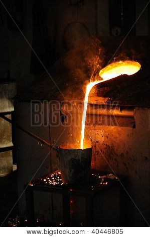 Foundry - Molten metal poured from lathe for casting