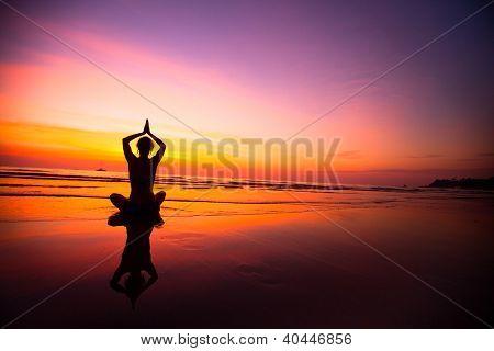 Silueta de mujer practicando yoga en la playa durante un hermoso atardecer.