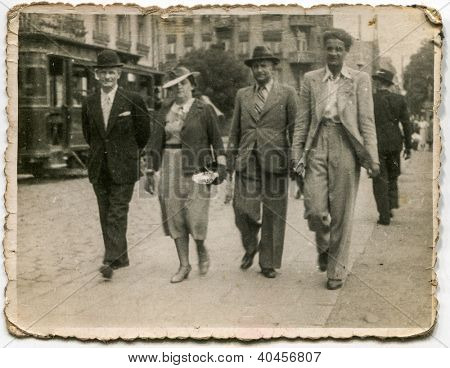 LODZ, POLAND, CIRCA 1935 - Vintage photo of family walking in the street with ancient tramway in background - Lodz, Poland, circa 1935