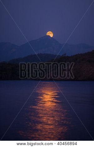 Moon rising over hills in Aegean Sea