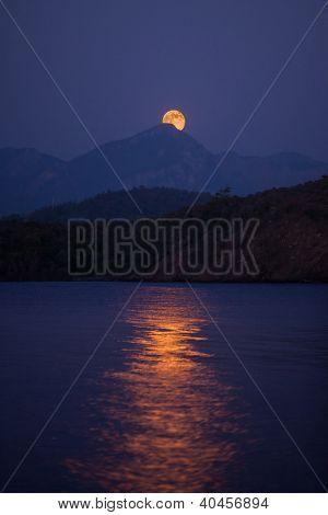 Moon rising over hills in Aegean Sea