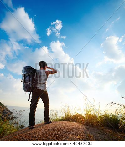 Tourist with backpack standing on top of a hill and enjoying the sunset sea view