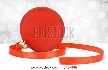One red christmas ball with ribbon on  background with stars and bokeh