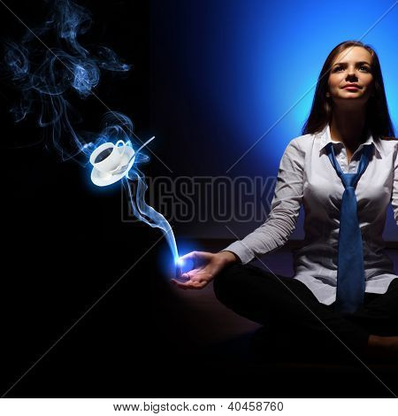 Businesswoman sitting and mediatating and a cup of coffee