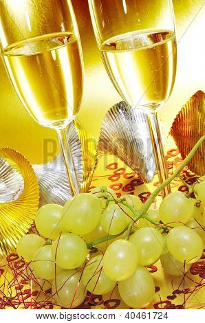 some glasses with spanish cava and a bunch of the grapes of luck, traditional on the New Year