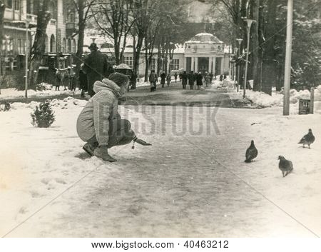 Vintage photo of young girl feeding pigeons in park (sixties)