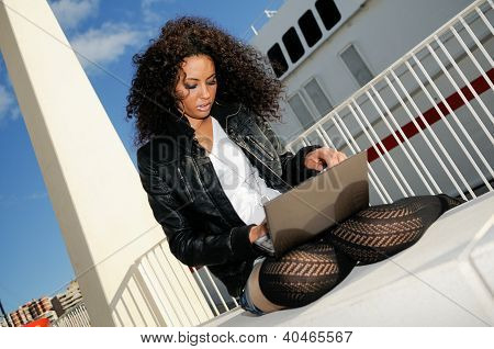 Happy relaxed african girl using a laptop in the street