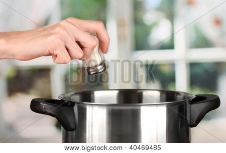 Hand adding salt using  salt shaker on bright background