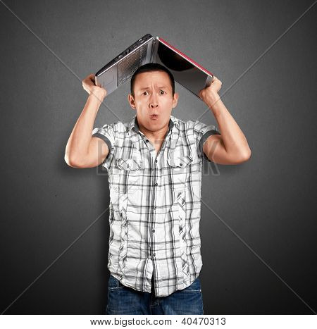 Asian man hides under the laptop in his hands