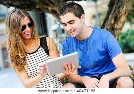 Casal atraente com computador Tablet no contexto urbano