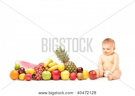 Baby boy sitting next to various fruits and vegetables isolated on white background