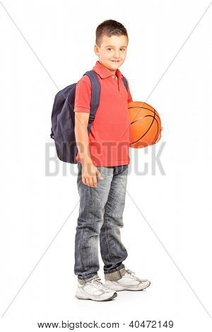 Full length portrait of a school boy with backpack holding a  basketball isolated on white background