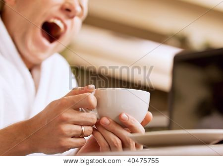 Yawning Sleepy Man With Cup Of Coffee In Hand