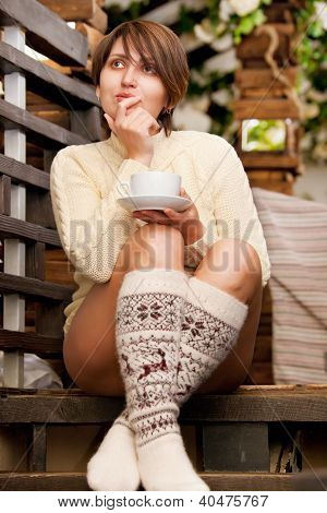 Attractive Woman With Cup Of Coffee Sitting At The Stairs