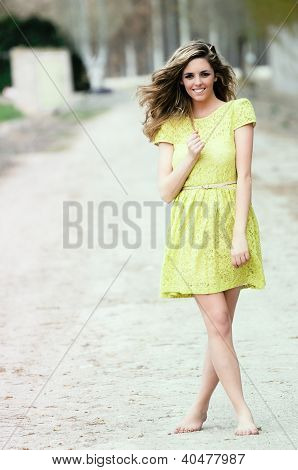 Beautiful Blonde Girl, Dressed With A Beige Dress, Standing In Rural Road