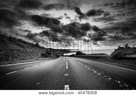 A road winds off into the distance, black and white