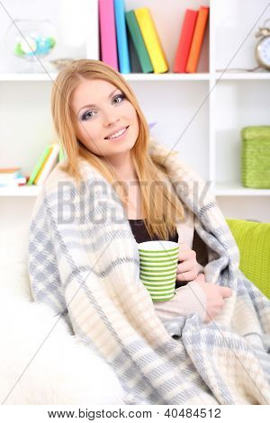Attractive young woman sitting on sofa, holding cup with hot drink, on home interior background