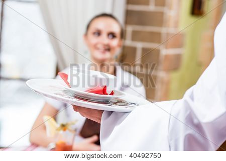 waiter brings a dish for a nice woman