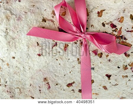 Closeup of hand made paper with rose petals and pink bow