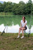 pic of fisherwomen  - Brunette Woman Fishing at a lake with green water - JPG