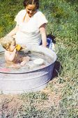 stock photo of washtub  - Vintage photo of pregnant mother and daughter bathing in a washtub  - JPG